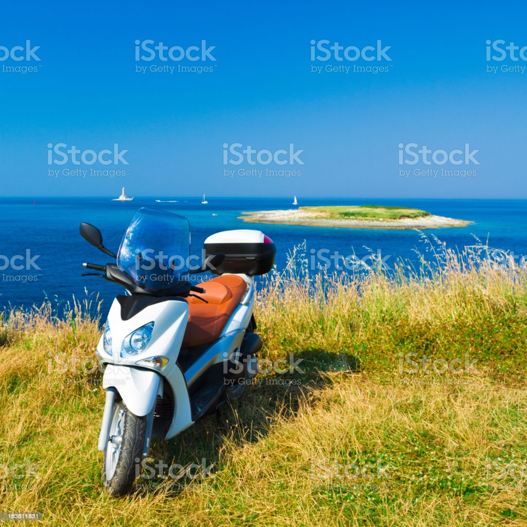 Vespa sitting in front of an ocean with an island behind royalty-free stock photo