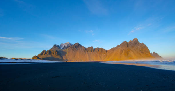 vestrahorn iceland, during golden hour vestrahorn iceland during winter with black sand beach, and frozen over salt water black sand stock pictures, royalty-free photos & images