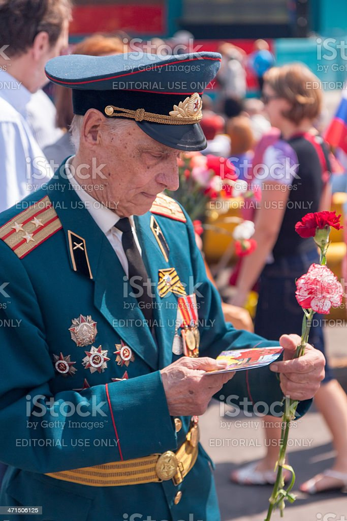 Veteran in uniform with awards looks at greeting card royalty-free stock photo