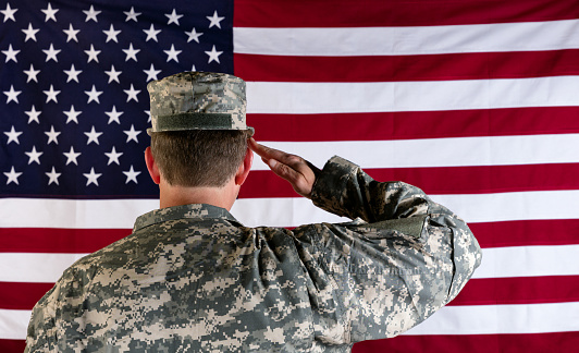 istock Veteran male solider saluting the flag of USA 532880372