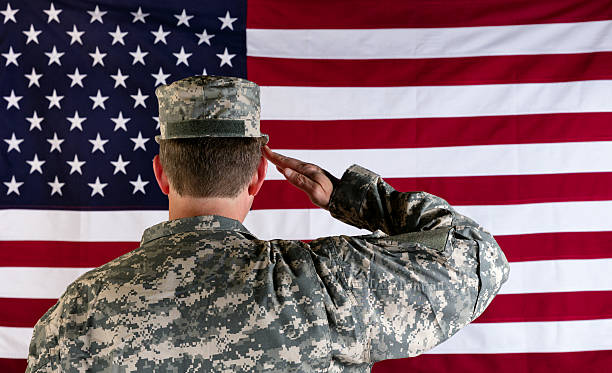 veteran male solider saluting the flag of usa - saluting stock photos and pictures