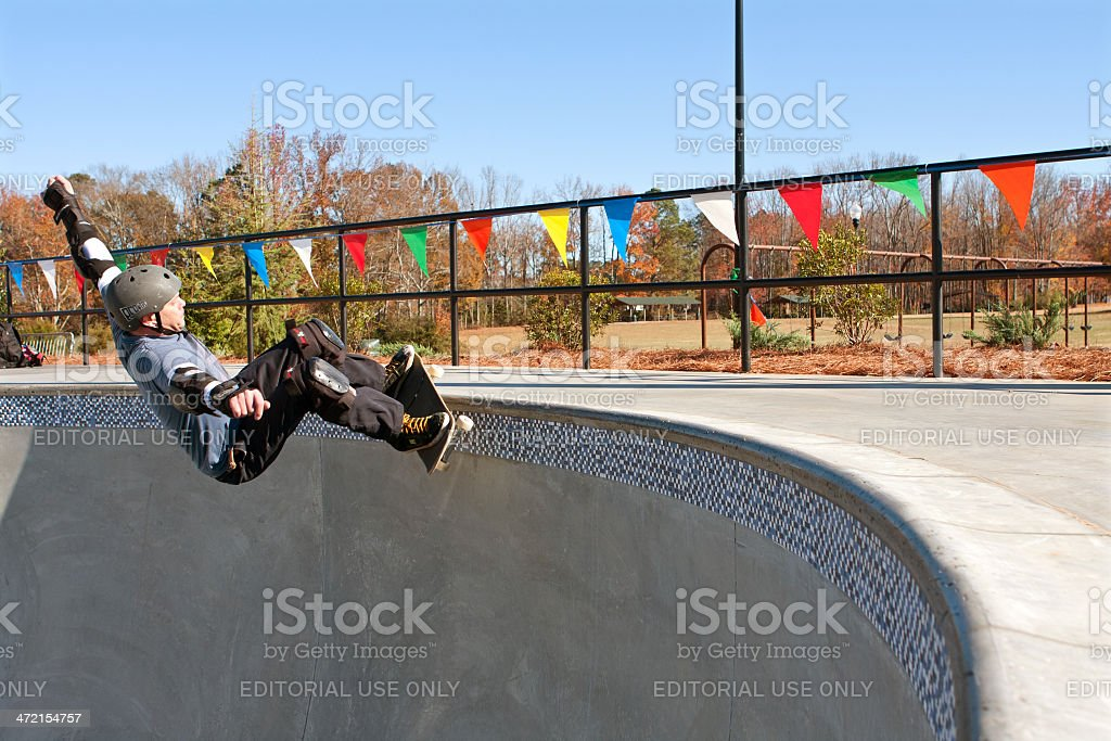 Veteran Skateboarder Grinds Along Top Of Big Bowl stock photo
