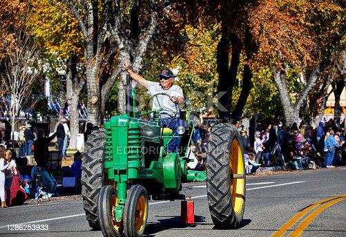 istock Veteran Waving on a Tractor in Veteran's Day Parade 1286253933