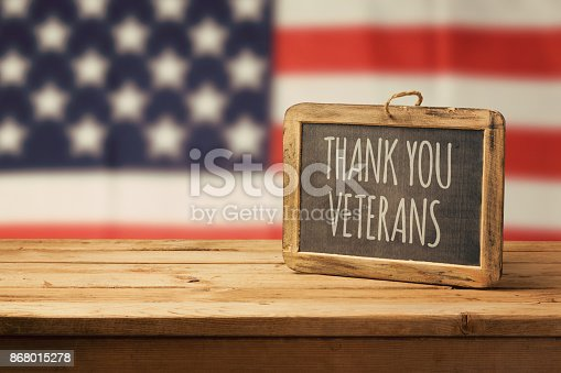 istock Veterans day background with chalkboard on wooden table and USA flag 868015278