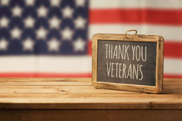 Veterans day background with chalkboard on wooden table and USA flag stock photo