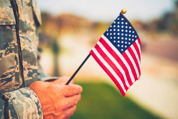 Veteran's Day in America. Soldier with American Flag stock photo