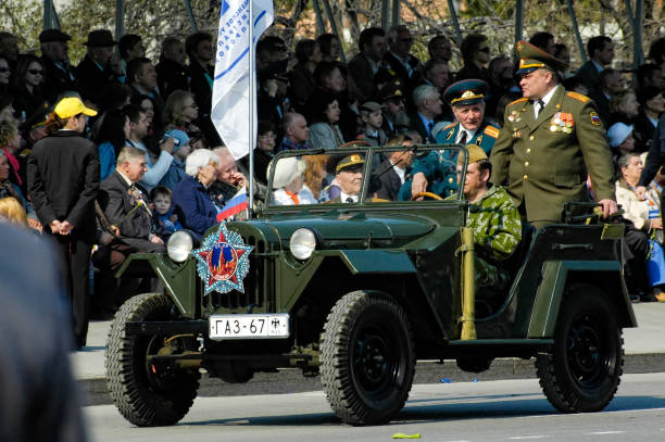 Veterans of World War 2 on parade Tyumen, Russia - May 9. 2006: Parade of Victory Day in Tyumen. Soldier in World War 2 uniform rolls veterans of war on GAZ-69 offroad vehicle willys stock pictures, royalty-free photos & images