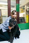 A Veterinary Nurse taking a dog through a door