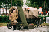 istock Vetka, Belarus. Young Woman Reenactor Dressed As Russian Soviet Red Army Soldier Of World War II Standing Near Peasant Cart. WWII Equipment Of Red Army. 1069788652