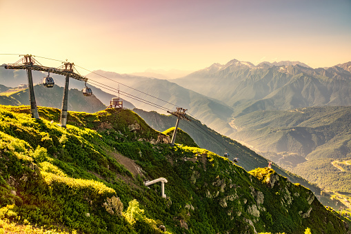 Vew in the summer sunset to the ski resort Rosa Khutor from the top of the Aibga range. The cable car is illuminated by the orange sunset. Beautiful orange sunset in mountains