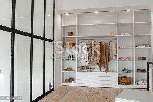 Vew on open space minimalistic scandinavian white wood walk in closet with wardrobe in neutral beige colors