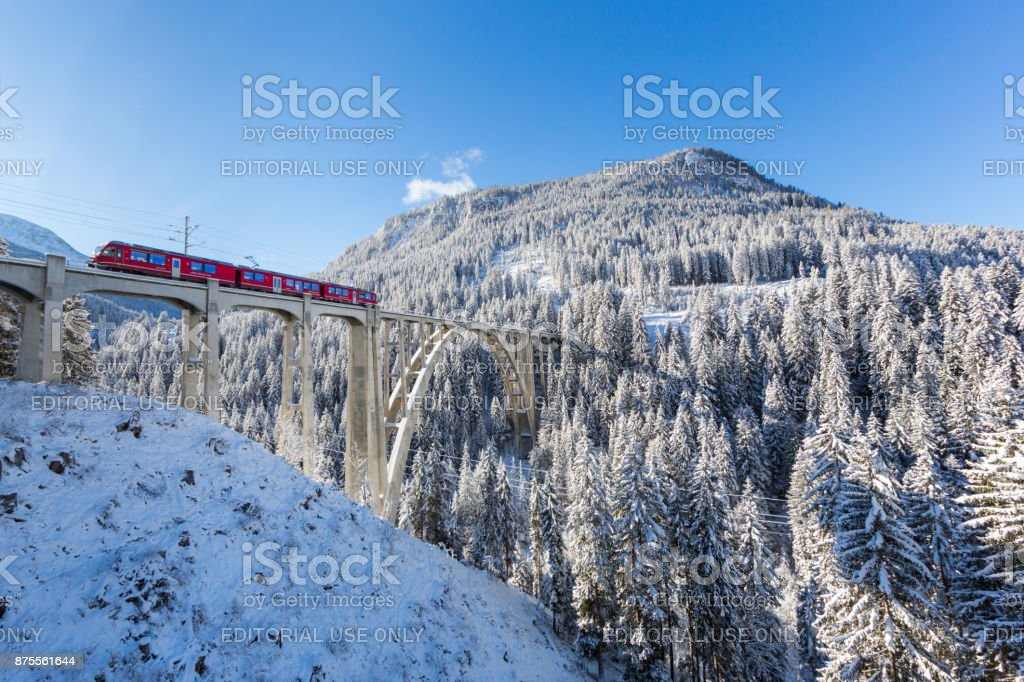 viaduct Langwies in Switzerland in sunshine, winter, snow, blue sky stock photo
