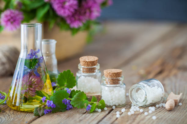 Vials of tincture or infusion of healthy herbs, bottles of homeopathy globules and healthy herbs on table. Alternative medicine concept. stock photo