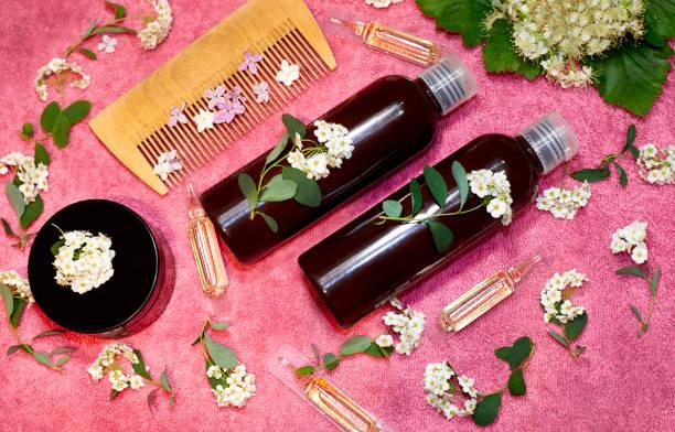 用粉紅色毛巾在鮮花上用護髮用品的瓶子。 - 護髮用品 個照片及圖片檔
