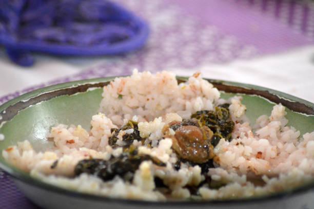Viande de porc et feuilles de sornet accompagné de riz Recette traditionnelle malgache: Viande de porc et feuilles de sornet ou brèdes sur une assiette accompagné de riz. riz stock pictures, royalty-free photos & images