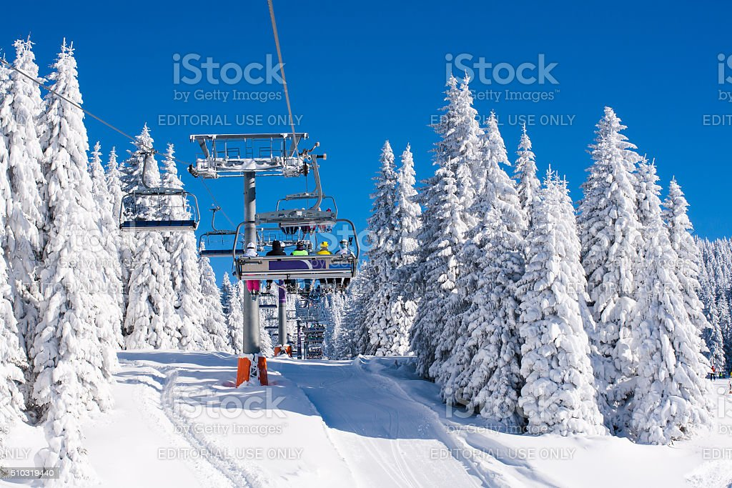 Vibrant active people winter image with skiers on ski lift stock photo
