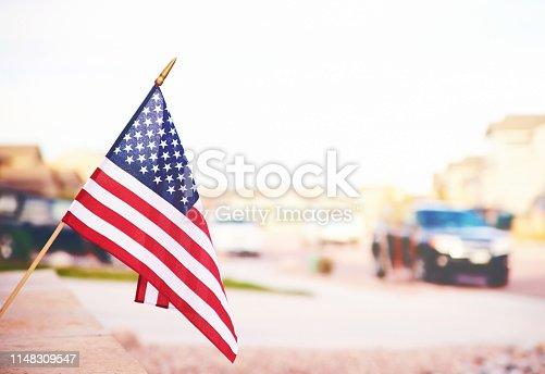 Vibrant American flag in summer sunshine with defocused street