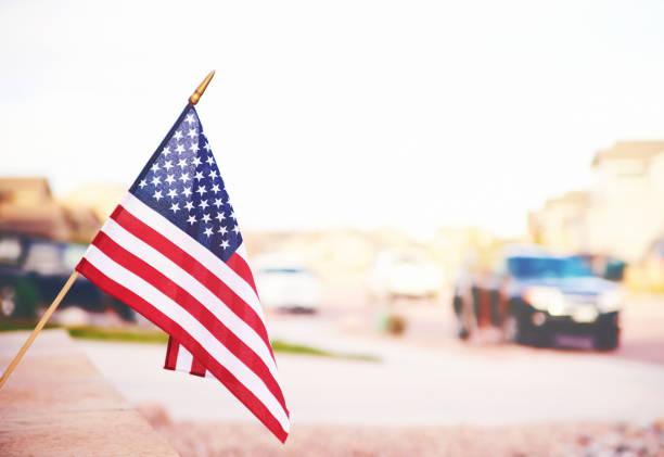 Lebendige amerikanische Fahne bei sommerlichem Sonnenschein mit defokussierter Straße – Foto