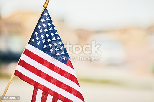 Vibrant American flag in summer sunshine with defocused street