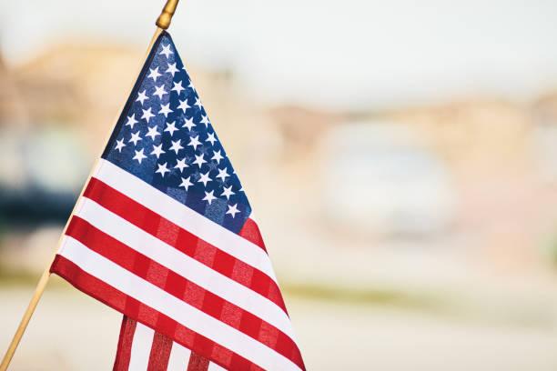 Lebendige amerikanische Flagge im Sommersonnenschein mit defokussierten Straße – Foto