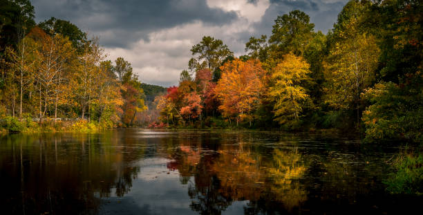 Vibrant autumn foliage reflected in Swartswood Lake at Swartswood Lake State Park, Stillwater, New Jersey stock photo