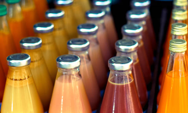 Vibrant Bottles of Juice Lined Up, Close-Up Vibrant Bottles of Juice Lined Up, Close-Up vegetable juice stock pictures, royalty-free photos & images