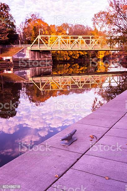 Photo of Vibrant Bright Autumn Morning Erie Canal Foliage and Bridge Reflections