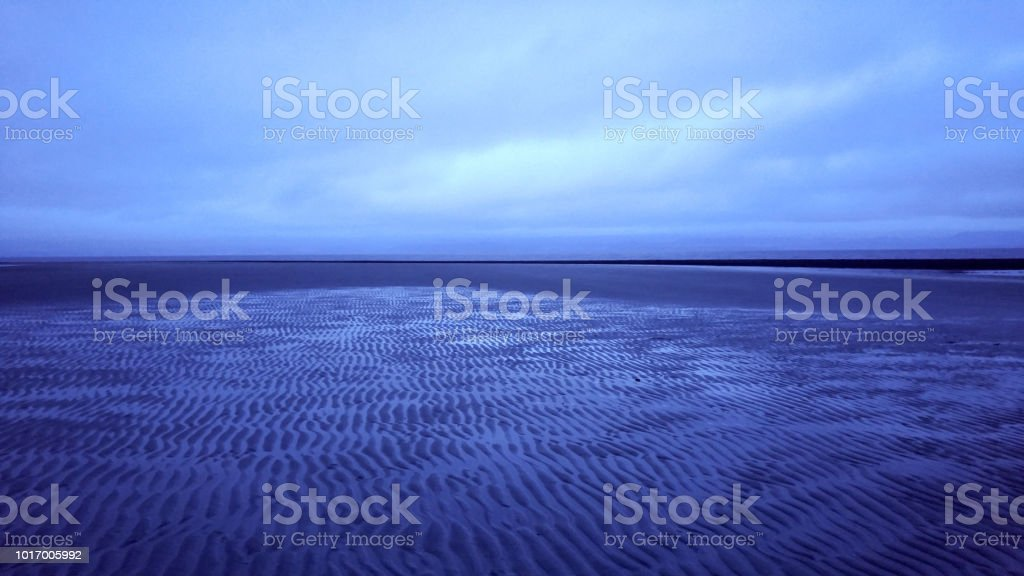 A vibrant cloudy color over ripples of sand at low tide by the ocean stock photo