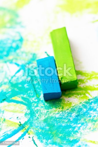 A vivid lime green and a bright turquoise pastel crayon on a sketchpad already marked and smudged by them.