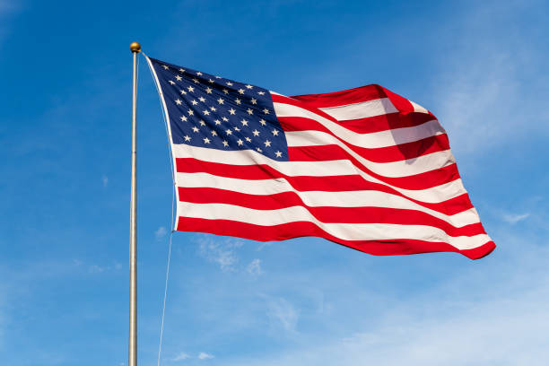 Vibrant colored American Flag waving in the wind, lit by natural sunlight American Flag waving in the wind, with beautiful red white and blue colors. flagpole stock pictures, royalty-free photos & images