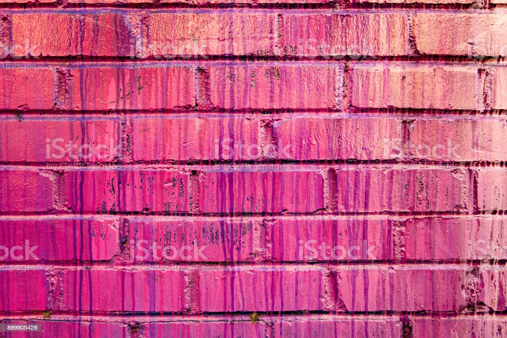 A vibrant colorful brick wall covered in streaks and drips of glossy paint stock photo