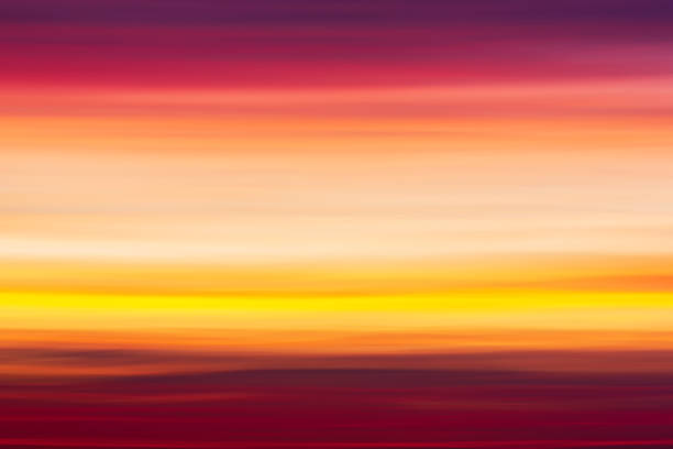 Vibrant colorful striped background of red, pink, purple and orange clouds in blurry sunset sky stock photo