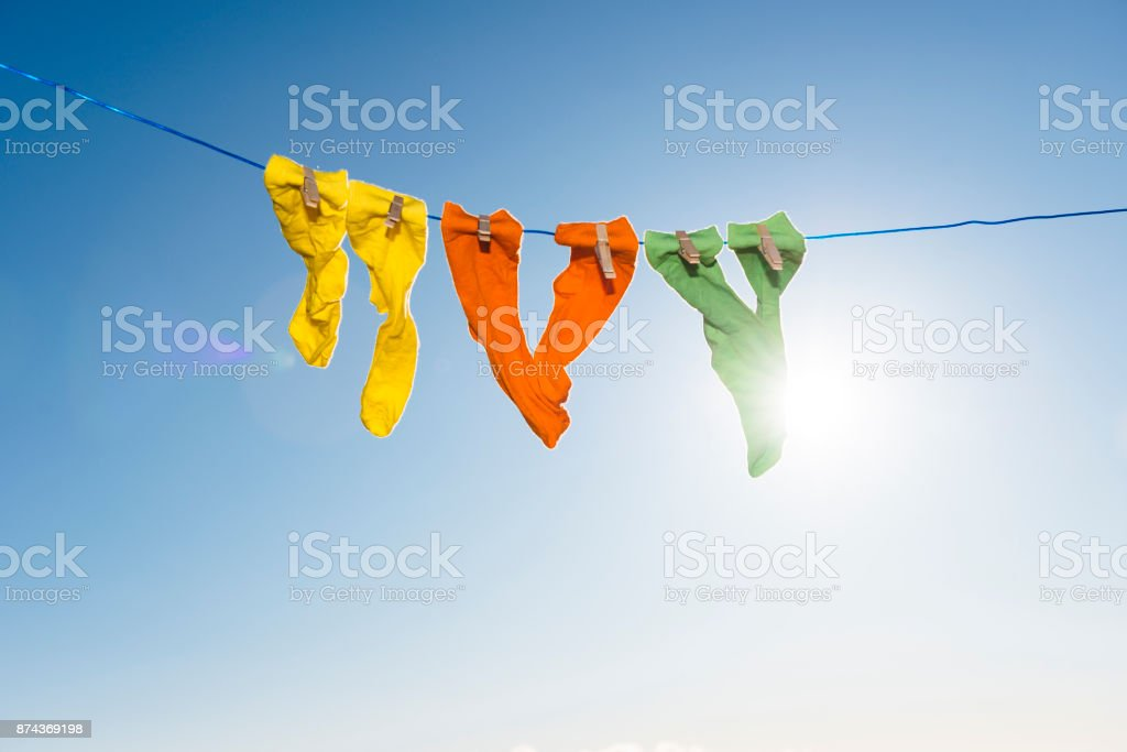 Vibrant coloured socks on a washing line against a blue sky. stock photo