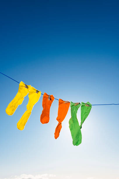 vibrant coloured socks on a washing line against a blue sky. - washing line stock photos and pictures