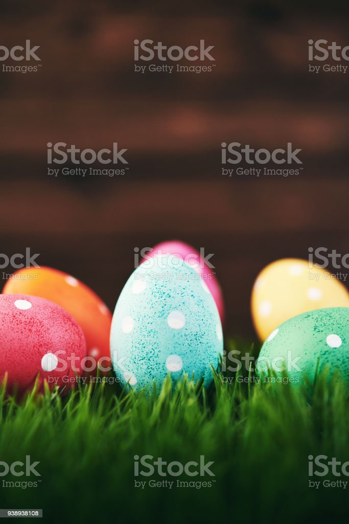 vibrant easter background with polka dot easter eggs in grass royalty free stock photo