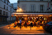 """""""Paris, France - June 27, 2012: Diners and serves at the Cafe Le Nazir in the Montmartre district of Paris as the evening settles in."""""""