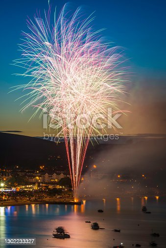Colourful fireworks exploding into the vibrant sunset skies above a pretty seaside town and tranquil bay below.