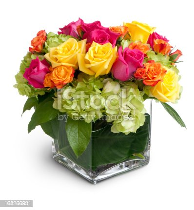 Vibrant multicolored flowers in a clear square crystal vase, isolated over a white background with cast shadow. Pink,yellow and orange roses are arranged with green hydrangea. Canon 5D MarkII.