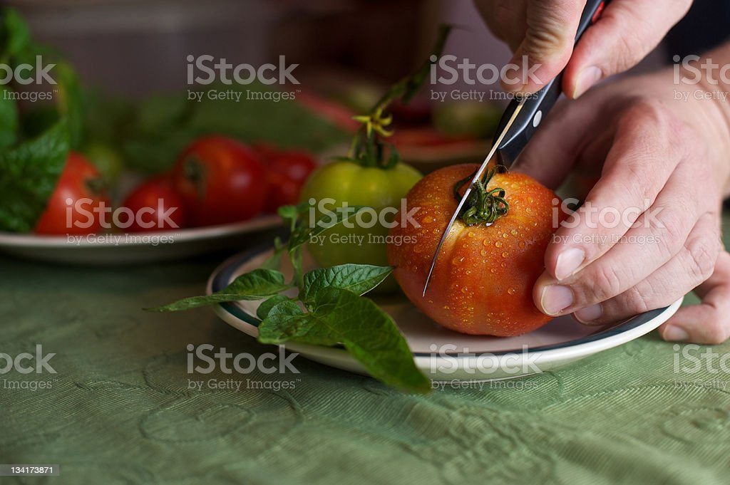 Vibrant Fresh Orange-Red Tomato being Cut stock photo