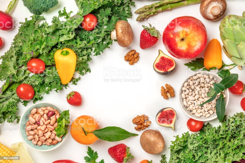 Vibrant fresh vegetables, fruits, cereals, and mushrooms on white background with copyspace stock photo