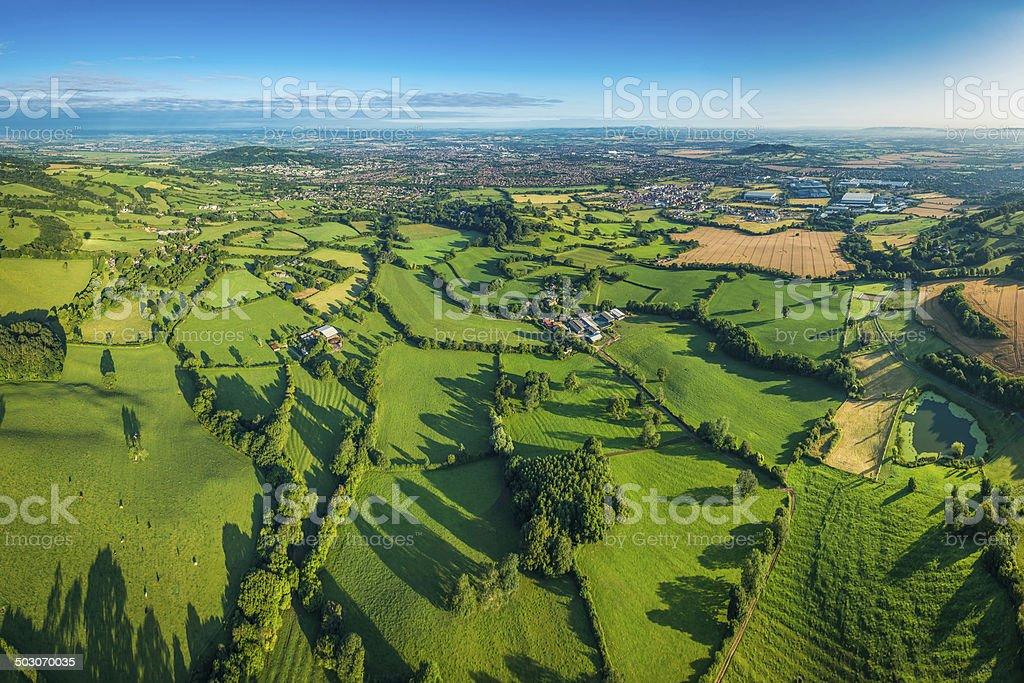 Vibrant green fields lush pasture farmland around town aerial photo stock photo