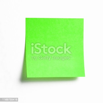 istock Vibrant green sticky note with shade isolated on white 1169755416