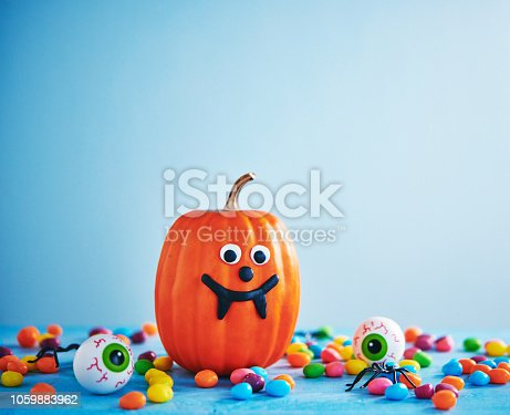 598064660istockphoto Vibrant Halloween image with pumpkin, candy and eyeballs 1059883962