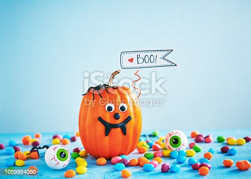 598064660istockphoto Vibrant Halloween image with pumpkin, candy and eyeballs 1059884050