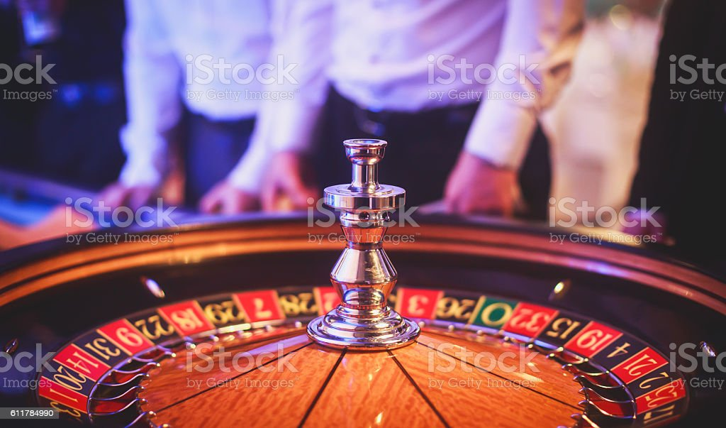 Vibrant image of multicolored casino table, people in the background stock photo
