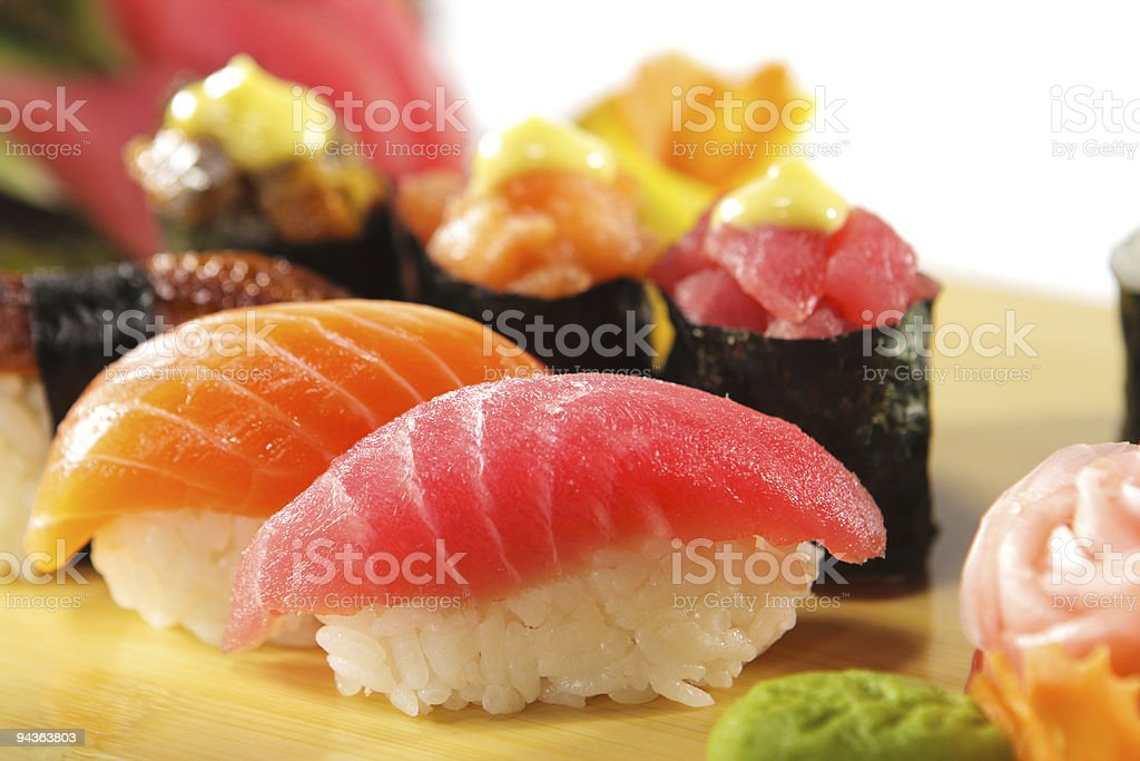 Vibrant Japanese sushi bites & rolls on a wooden table stock photo