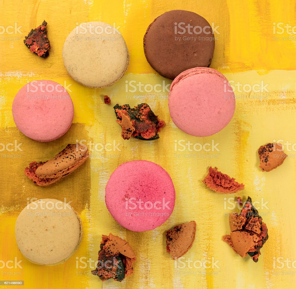 Vibrant macarons with crumbs on bright yellow texture foto stock royalty-free