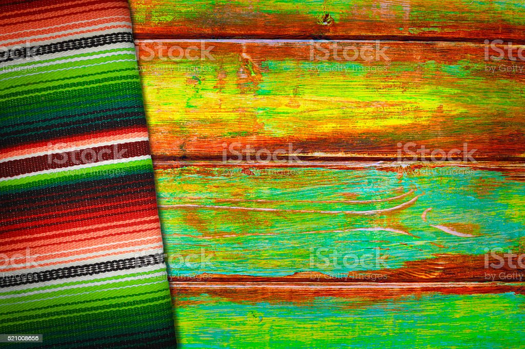 Vibrant Mexican Serape Blanket and Wood Background stock photo