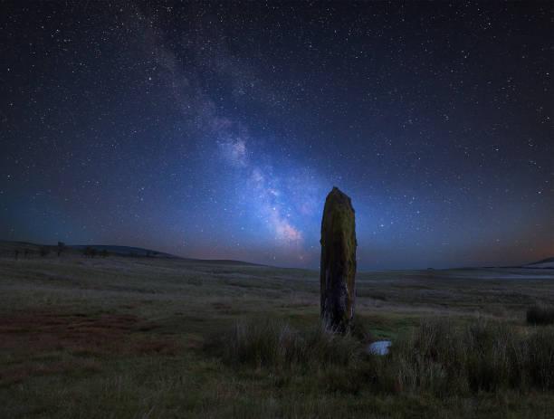 lebendige milchstraße zusammengesetztes bild über landschaft des alten prähistorischen steinen in wales - sternmoos stock-fotos und bilder