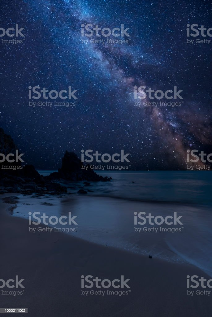 Vibrant Milky Way composite image over landscape of Barafundle Bay on Pembrokeshire Coast in Wales stock photo